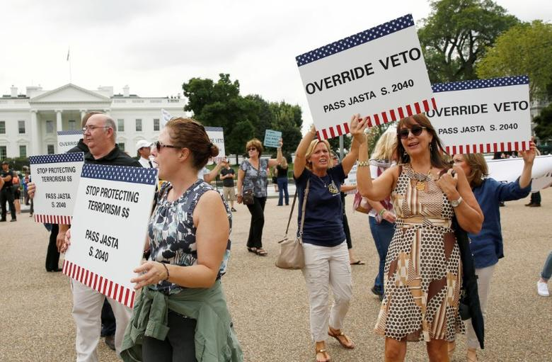 Protesters and family members of 9/11 victims hold placards in front of the White House regarding President Barack Obama's threatened veto of the Justice Against Sponsors of Terrorism Act (JASTA) in Washington, U.S., September 20, 2016.   REUTERS/Gary Cameron
