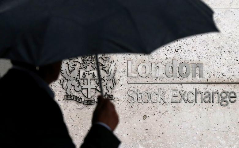 A man shelters under an umbrella as he walks past the London Stock Exchange in London, Britain August 24, 2015. REUTERS/Suzanne Plunkett