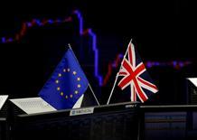 Una bandera británica y una de la Unión Europea frente a un monitor que muestra la gráfica de fluctuación del yen japonés contra el dólar estadounidense, en una correduría en Tokio. 27 de junio de 2016. El crecimiento económico se empantanará este año y el próximo con tasas de interés que no se han visto desde la crisis financiera porque se frenó el avance de la globalización, advirtió el miércoles la OCDE. REUTERS/Toru Hanai