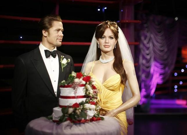 Wax models of actors Brad Pitt and Angelina Jolie are pictured with a wedding cake and a bridal veil in celebration of their recent wedding, at the Madame Tussauds attraction in Sydney, August 29, 2014. REUTERS/Jason Reed/Files
