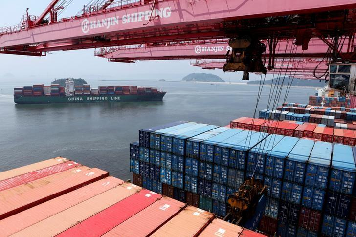 A crane carries a container from a Hanjin Shipping ship at the Hanjin container terminal as a China Shipping Line ship (L) arrives at the Busan New Port in Busan, about 420 km (261 miles) southeast of Seoul, August 8, 2013.  REUTERS/Lee Jae-Won/Files