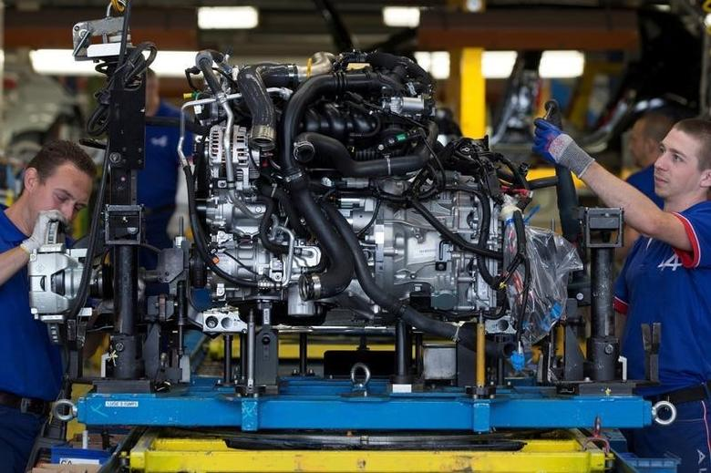 Employees of French carmaker Renault handle a new Clio RS engine on the assembly line at Renault factory in Dieppe, France, September 1, 2015. REUTERS/Philippe Wojazer/File Photo