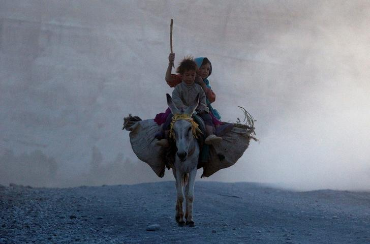 Ethnic Afghan Hazara children return home on a donkey to their village on the outskirts of Bamiyan, located in central Afghanistan August 15, 2009.  REUTERS/Adrees Latif/File Photo