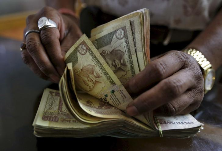 A money lender counts Indian rupee currency notes at his shop in Ahmedabad, in this May 6, 2015 file photo. REUTERS/Amit Dave/Files