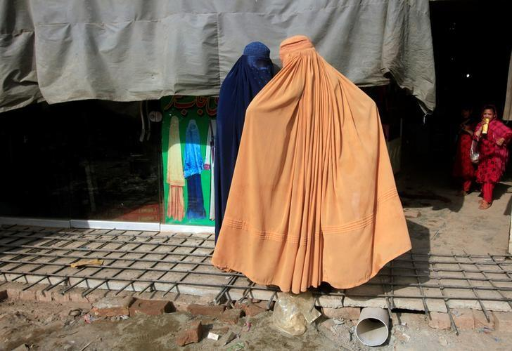 Afghan women, clad in burqas, stand outside a shop at a market in Peshawar, Pakistan June 29, 2016. REUTERS/Fayaz Aziz