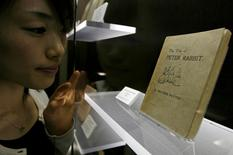 "Assistant Yui Takeda looks at the first edition of ""The Tale of Peter Rabbit"", privately printed by the author Beatrix Potter in 1901, as she poses for a picture at the Beatrix Potter Museum in Higashi Matsuyama, north of Tokyo, Japan May 10, 2007.      REUTERS/Kiyoshi Ota/File Photo"