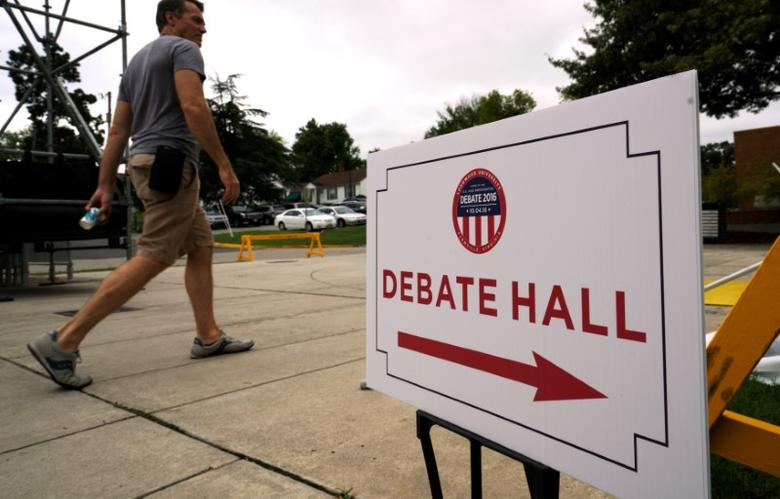 A man walks past a sign for the U.S. vice-presidential debate at Longwood University in Farmville, Virginia October 2, 2016. LREUTERS/Rick Wilking
