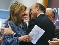 La presidenta de la CNMV, Elvira Rodríguez, anunció el lunes que no continuará al frente del regulador del mercado de valores español cuando expire su cargo esta semana, en medio de una parálisis política que se prolonga nueve meses que impide la renovación de determinados cargos públicos. En la imagen de archivo, Rodríguez (izq) recibe un abrazo del actual ministro de Economía en funciones, Luis de Guindos, durante una de sus primeras apariciones públicas como jefa de la CNMV, el 15 de octubre de 2012. REUTERS/Andrea Comas