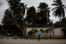 """Женщина с зонтом в городе Ле-Ке в Гаити. 3 октября 2016 года. Гаитяне, живущие в шатких прибрежных хижинах, в спешке ищут укрытие от приближающегося к острову урагана """"Мэттью"""" - самого мощного в Карибском море за последние девять лет, вызвавшего штормовые волны, сильные ветер и дождь. REUTERS/Andres Martinez Casares"""