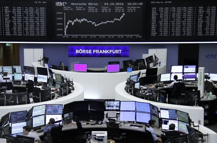 Traders work at their desks in front of the German share price index, DAX board, at the stock exchange in Frankfurt, Germany, October 4, 2016. REUTERS/Staff/Remote