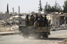 Повстанцы проезжают мимо разрушенных зданий в окрестностях на севере Алеппо, Сирия, 2 октября 2016 года. Повстанцы сообщили во вторник, что отразили наступление армии президента Башара Асада на юге Алеппо, где российские самолеты бомбили жилые районы на фоне попыток мирового сообщества вернуться к переговорам, вести которые с Москвой отказался на этой неделе Вашингтон.  REUTERS/Khalil Ashawi