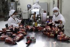 Trabajadores en una planta procesadora de café en Bogotá, mayo 14, 2012. La producción colombiana de café bajó un 2 por ciento en septiembre con respecto al mismo mes del año anterior, como consecuencia del impacto del fenómeno climático El Niño y del rezago de una huelga de camioneros, informó el miércoles la Federación Nacional de Cafeteros.  REUTERS/Fredy Builes