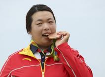 Shanshan Feng of China bites on her bronze medal in women's Olympic golf competition. REUTERS/Kevin Lamarque