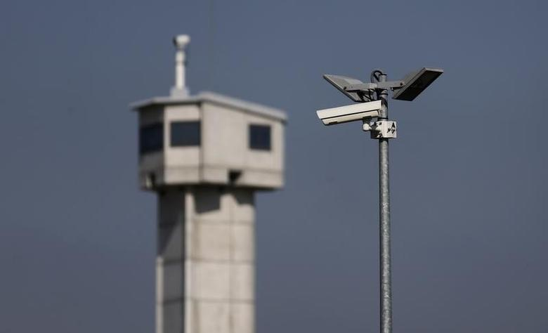 A surveillance camera is seen in front of a prison watchtower at the Reau penitentiary, near Paris, September 24, 2013. REUTERS/Christian Hartmann/Files