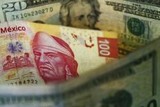 Un billete de 100 pesos mexicanos en medio de unos billetes de 20 dólares, mar 10, 2015. El drama de las elecciones de Estados Unidos y un debilitamiento de la economía harán que el peso mexicano caiga a un mínimo histórico de 20 por dólar, según proyectaron algunos estrategas cambiarios el jueves en un sondeo de Reuters.  REUTERS/Edgard Garrido