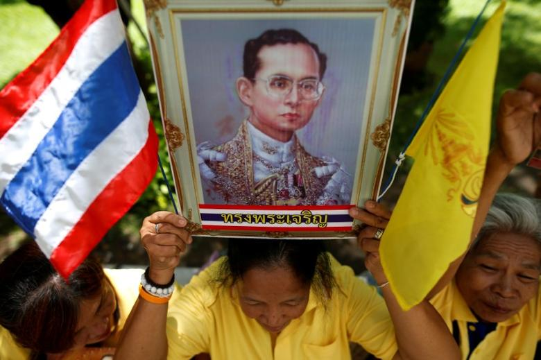 A well-wisher holds a picture of Thailand's King Bhumibol Adulyadej at the Siriraj hospital where he is residing, in Bangkok, Thailand, June 9, 2016. REUTERS/Athit Perawongmetha/Files