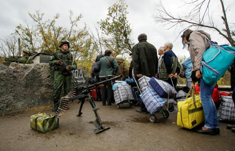 Members of the self-proclaimed Luhansk People's Republic forces stand guard as residents queue at pass through a check point located on the troops contact line between pro-Moscow rebels and Ukrainian troops, in the settlement of Stanytsia Luhanska in Luhansk region, Ukraine, October 9, 2016. REUTERS/Alexander Ermochenko