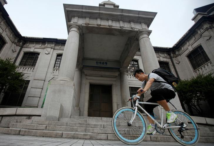A man gets on a bicycle in front of the Bank of Korea in Seoul August 9, 2012.   REUTERS/Kim Hong-Ji/Files
