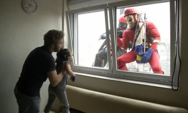 10月11日、サンパウロにある小児病院でバットマンなどのスーパーヒーローに扮して窓ふきをする2人の作業員が出現し、入院している子供たちを元気づけた。写真は動画から(2016年 ロイター)