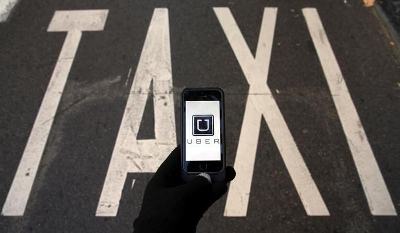 The logo of car-sharing service app Uber on a smartphone over a reserved lane for taxis in a street is seen in this photo illustration taken December 10, 2014.   REUTERS/Sergio Perez/Illustration/Files