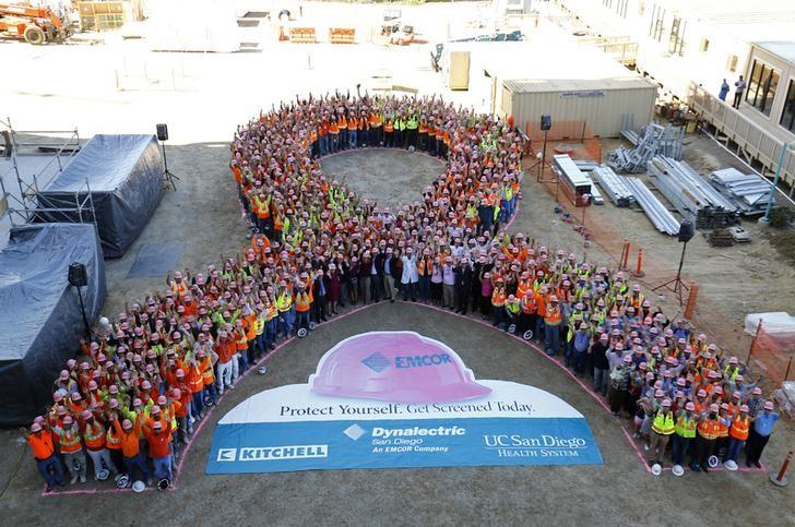 Construction workers and hospital employees wear pink hard hats and form a giant pink ribbon to promote the start of Breast Cancer Awareness Month, at the UC San Diego Jacobs Medical Center construction site in La Jolla, California, September 30, 2014.  REUTERS/Mike Blake/File Photo