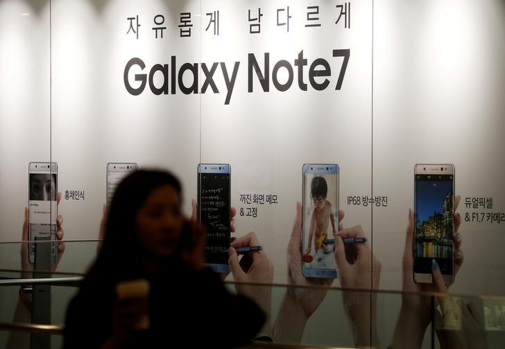 A woman talking on her mobile phone walks past an advertisement promoting Samsung Electronics' Galaxy Note 7 at company's headquarters in Seoul, South Korea, October 11, 2016.   REUTERS/Kim Hong-Ji/Files