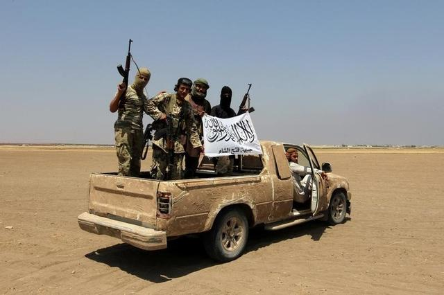 Fighters of the Syrian Islamist rebel group Jabhat Fateh al-Sham cheer on a pickup truck after a Russian helicopter was shot down in the north of Syria's rebel-held Idlib province, Syria, August 1, 2016. REUTERS/Ammar Abdullah/File Photo