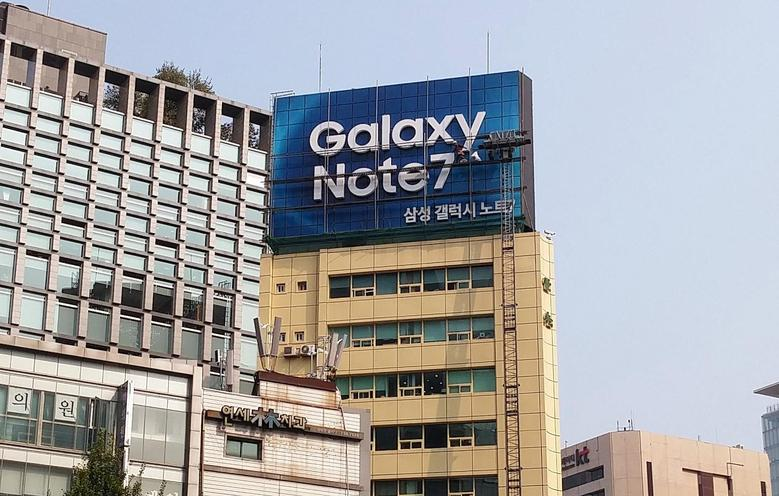 Workers take a billboard of Samsung Electronics' Galaxy Note 7 off from atop a building in central Seoul, South Korea, October 14, 2016. REUTERS/Staff