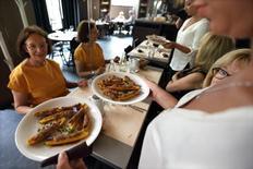 Una camarera sirve platos a unas clientas en un restaurant en París, Francia. 23 de julio de 2013. Los precios más altos en restaurantes y cafés además de alquileres y tabaco impulsaron al alza la inflación en la zona euro en septiembre, según datos publicados el lunes, compensando los bajos precios de los combustibles y el gas. REUTERS/Philippe Wojazer