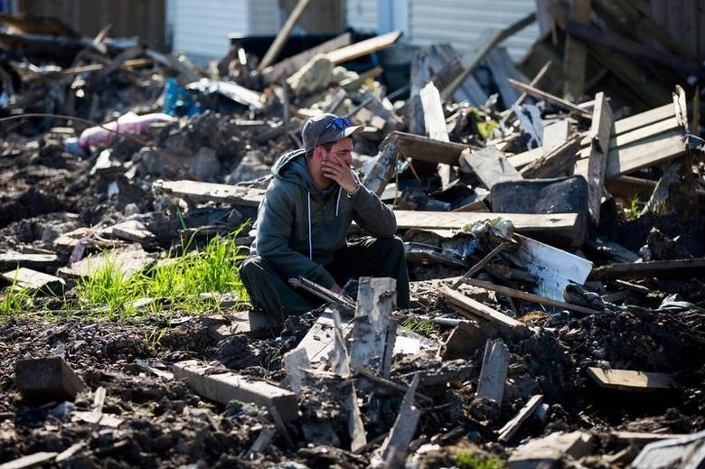 FILE PHOTO - A resident looks over the damage in the Timberlea neighbourhood as thousands of evacuees who fled a massive wildfire begin to trickle back to their homes in Fort McMurray, Alberta, on Canada June 2, 2016. REUTERS/Topher Seguin/File Photo