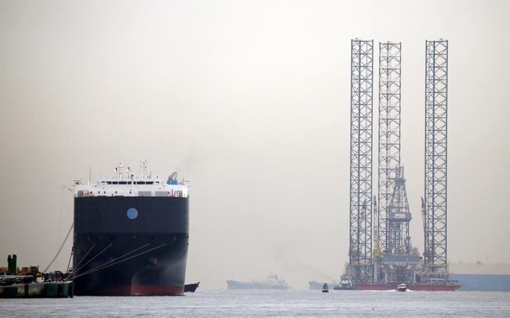 Part of an offshore drilling platform (R) is towed past a car carrier docked at Singapore port November 2, 2015. REUTERS/Tim Wimborne/File Photo