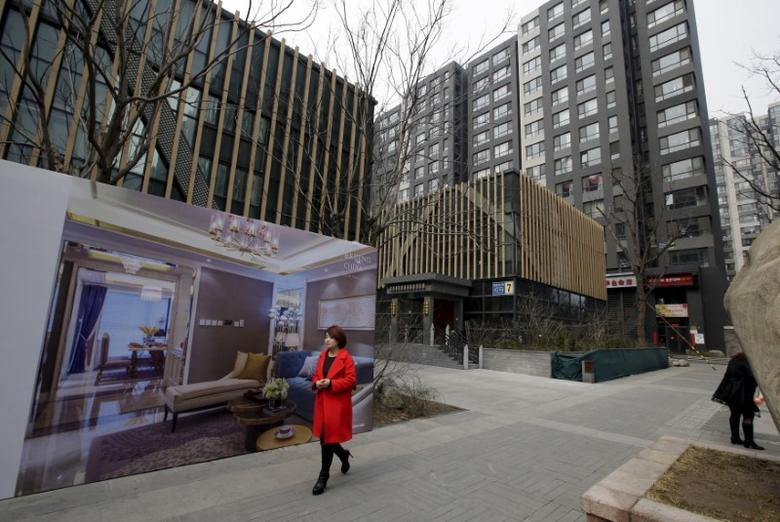 A woman walks past a property poster outside luxury apartment blocks in central Beijing, China, March 15, 2016. REUTERS/Jason Lee