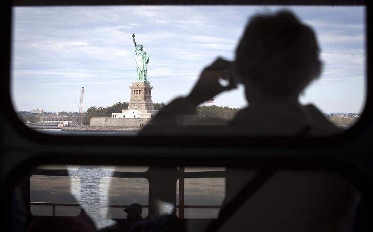 The Statue of Liberty is pictured from the Staten Island Ferry as people are reflected in windows in New York, October 12, 2013.  REUTERS/Carlo Allegri