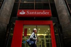 Banco Santander anunció el miércoles un aumento del 1 por ciento interanual en el beneficio neto del tercer trimestre, superando las previsiones de los analistas en unas cifras que se vieron impulsadas por la recuperación de su negocio brasileño. En la imagen de archivo, una mujer pasa frente a una sucursal de Banco Santander en Río de Janeiro el 19 de agosto de 2014. REUTERS/Pilar Olivares