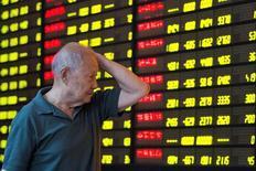 Китайский инвестор смотрит на табло с информацией об акциях/ Фондовые индексы Китая снизились по итогам торгов пятницы, так как инвесторы анализировали корпоративные отчеты, чтобы оценить здоровье китайской экономики, при этом слабость акций ведущих инфраструктурных компаний нивелировала подъем в финансовом секторе.  China Daily/via REUTERS