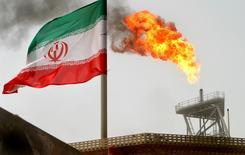 Una bandera de Irán cerca de una plataforma petrolera, en el Golfo. 25 de julio de 2005. La actual producción de petróleo de Irán llegó a casi 4 millones de barriles por día (bpd) y sus exportaciones han alcanzado 2,4 millones de bpd, dijo el director de la compañía estatal NIOC, citado el lunes por la agencia de noticias del Gobierno. REUTERS/Raheb Homavandi/File Photo