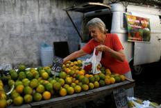 Una clienta selecciona naranjas de un puesto en un mercado callejero en Río de Janeiro, Brasil. 6 de mayo de 2016.Los volúmenes de ventas minoristas en Brasil, excluyendo automóviles y materiales de construcción, bajaron un 1,0 por ciento en septiembre frente a agosto, dijo el jueves el estatal Instituto Brasileño de Geografía y Estadística (IBGE).. REUTERS/Pilar Olivares/File Photo