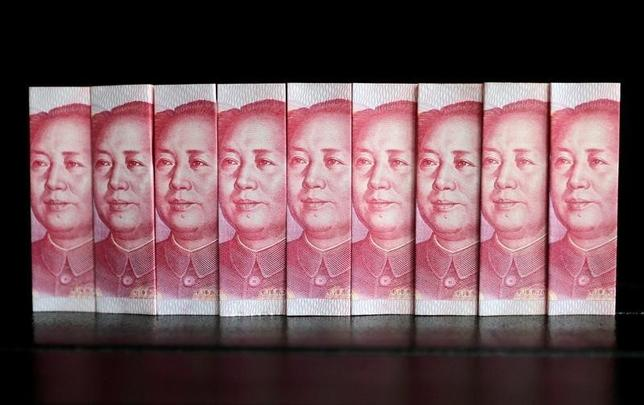 11月18日、中国の政策当局者は最近の人民元下落を気にかけていないが、心理的に重要な1ドル=7元を超えて急激に下落すると資本逃避を加速する可能性があることから介入する用意をしている。写真は人民元紙幣、2013年7月撮影(2016年 ロイター/Jason Lee)