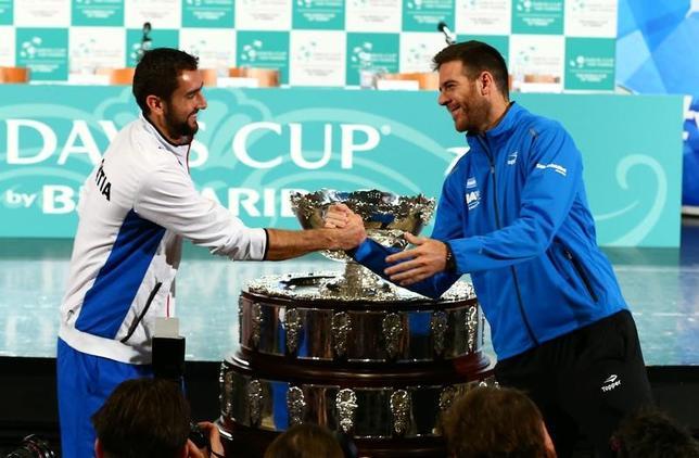 11月24日、男子テニスの国別対抗戦、デビスカップ(杯)の決勝が25日から27日にかけてクロアチアのザグレブアリーナで行われ、クロアチアとアルゼンチンが優勝を争う。写真左はフアンマルティン・デルポトロ(右)と握手するマリン・チリッチ(2016年 ロイター/Antonio Bronic)