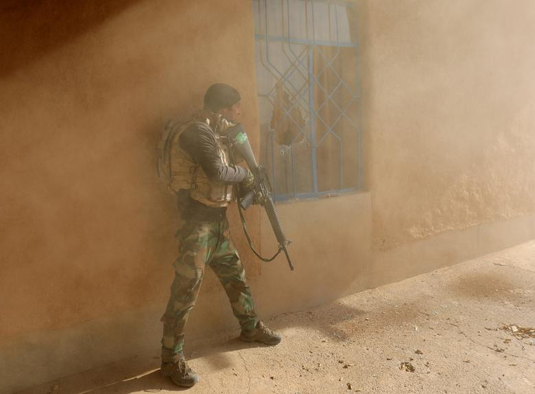 An Iraqi soldier searches a house during clashes with Islamic State fighters in Al-Qasar, southeast of Mosul. REUTERS/Goran Tomasevic