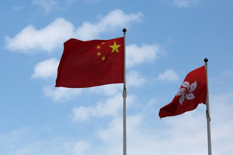 A Chinese national flag and a Hong Kong flag fly outside the Legislative Council in Hong Kong, China November 7, 2016, as China's parliament passed an interpretation of Hong Kong's Basic Law on Monday that says lawmakers must swear allegiance to the city as part of China.    REUTERS/Bobby Yip
