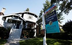 A real estate for sale sign is pictured in front of a home in Vancouver, British Columbia, Canada, September 22, 2016.    REUTERS/Ben Nelms/File Photo