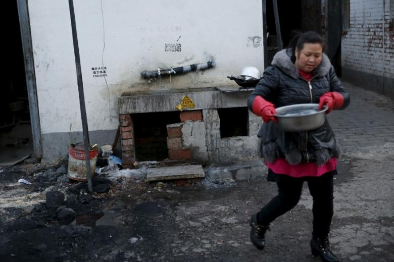 A migrant worker carries water for drinking and cooking from a public tap at a migrant workers' village in Beijing, China February 24, 2016.  REUTERS/Kim Kyung-Hoon