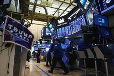 Предвыборный плакат Дональда Трампа на фондовой бирже в Нью-Йорке. 9 ноября 2016 года. Американский фондовый рынок завершил ноябрь большим подъёмом благодаря ралли после победы Дональда Трампа на президентских выборах, завершив, однако, торги среды преимущественно снижением из-за падения акций электроэнергетических и технологических компаний. REUTERS/Brendan McDermid