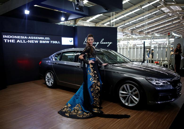 A model poses next to a BMW 7 Series car assembled locally during a media launch at a Gaya Motor assembly plant in Jakarta, Indonesia November 30, 2016. REUTERS/Darren Whiteside/File Photo