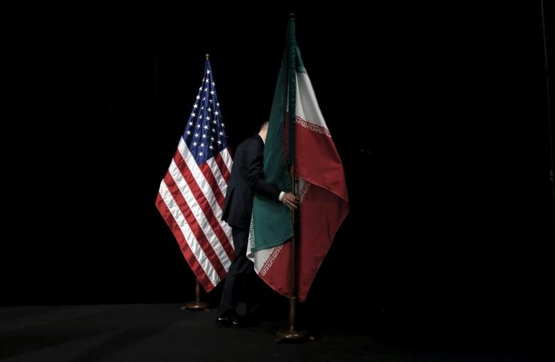 A staff member removes the Iranian flag from the stage after a group picture with foreign ministers and representatives of the U.S., Iran, China, Russia, Britain, Germany, France and the European Union during the Iran nuclear talks at the Vienna International Center in Vienna, Austria July 14, 2015. To match Analysis USA-ELECTION/IRAN      REUTERS/Carlos Barria/File Photo - RTX2STPS