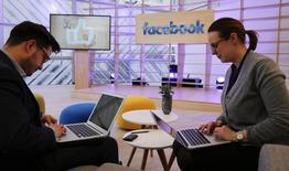La cantidad de dinero que se gastará en publicidad en medios sociales va a alcanzar a los ingresos publicitarios de los diarios para 2020, dijo el lunes un informe de una agencia de análisis.  En la imagen, gente trabaja con sus portátiles en la nueva sede de innovación de Facebook en Berlín, Alemania, el 24 de febrero de 2016.      REUTERS/Fabrizio Bensch
