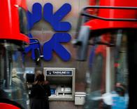 People stand near a branch of Royal Bank of Scotland (RBS) in London, Britain, November 1, 2013.   REUTERS/Luke MacGregor/File Photo