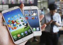 Слева - телефон производства Galaxy S4  Samsung Electronics, справа - iPhone 5 от Apple. Иллюстрация сделана в Меуле 13 мая 2013 года. Верховный суд США во вторник поддержал южнокорейского производителя смартфонов Samsung в дорогостоящей тяжбе с конкурентом, американской Apple. REUTERS/Kim Hong-Ji/File Photo