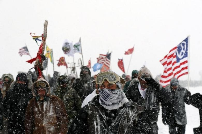 Veterans march with activists near Backwater Bridge just outside of the Oceti Sakowin camp during a snow fall as ''water protectors'' continue to demonstrate against plans to pass the Dakota Access pipeline adjacent to the Standing Rock Indian Reservation, near Cannon Ball, North Dakota, U.S., December 5, 2016.  REUTERS/Lucas Jackson